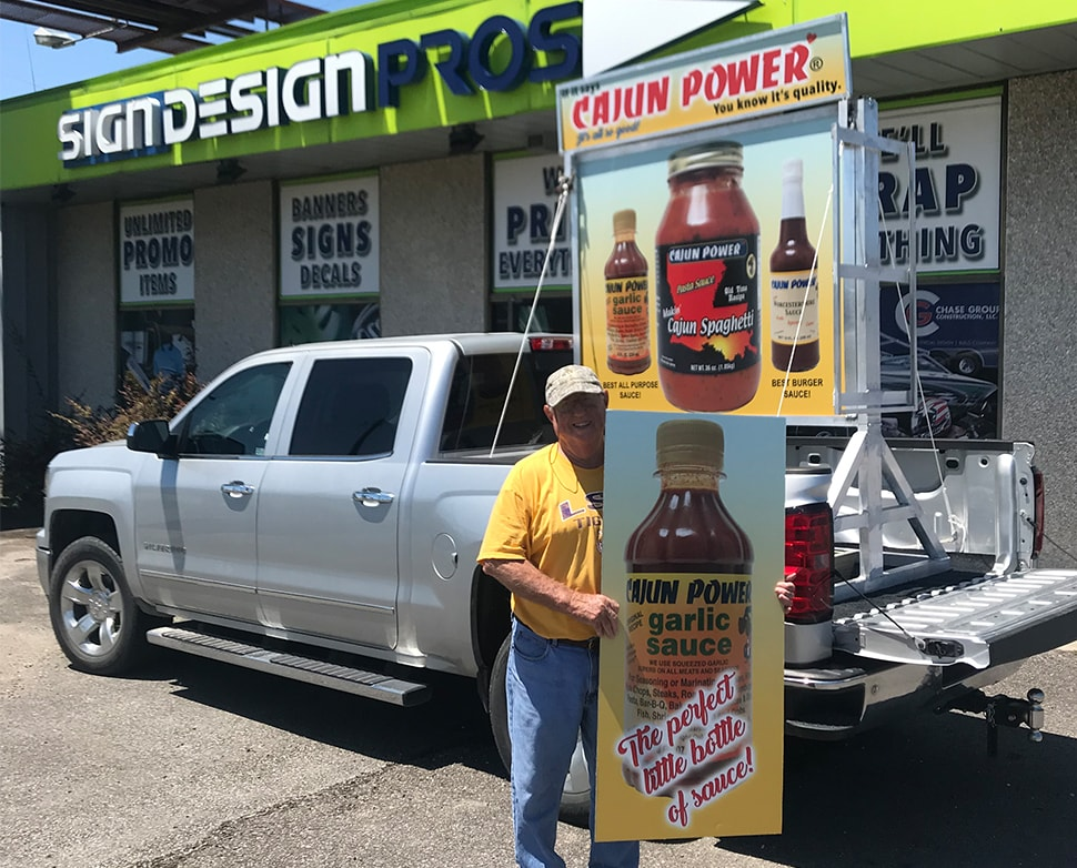 "gentleman holding ""Cajun Power"" flavor sign"